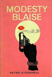 The cover of the book, Modesty Blaise. It is a peachy pink with a femme hand wearing bracelets holding a small gun and an isolated pair of lips is above the gun, blowing away the smoke