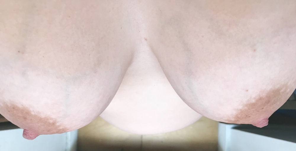 A view from above, showing my naked cleavage and looking down between to my 26 week pregnant belly