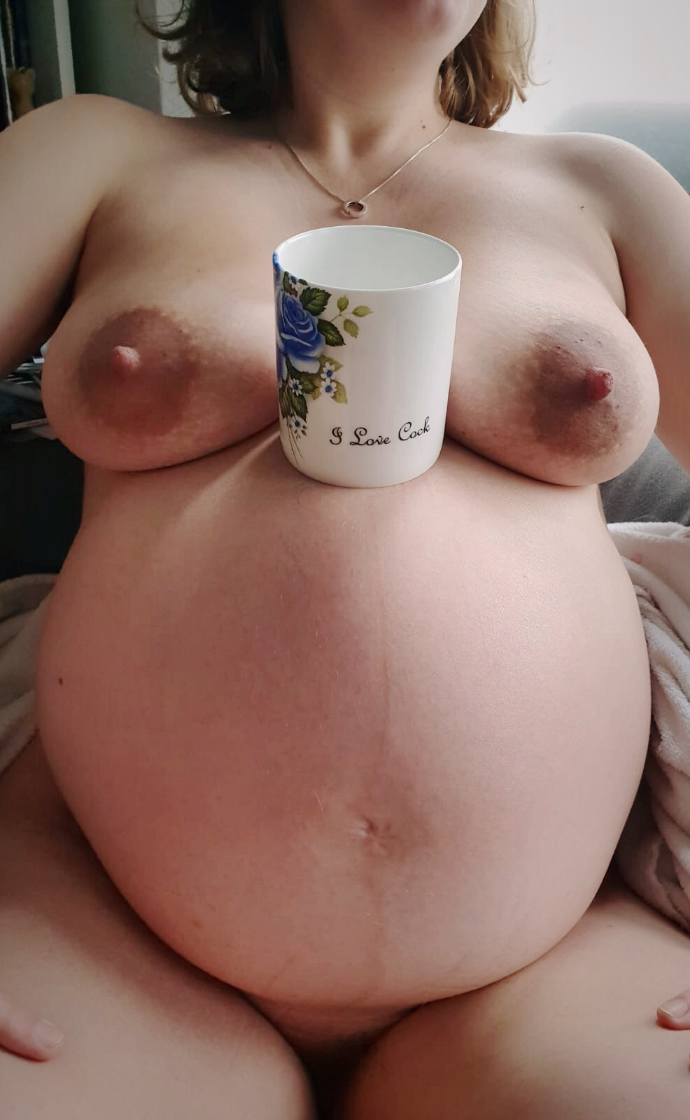 My naked 39 week pregnant torso with a tea cup that has 'I love cock' written in it balanced between my breasts