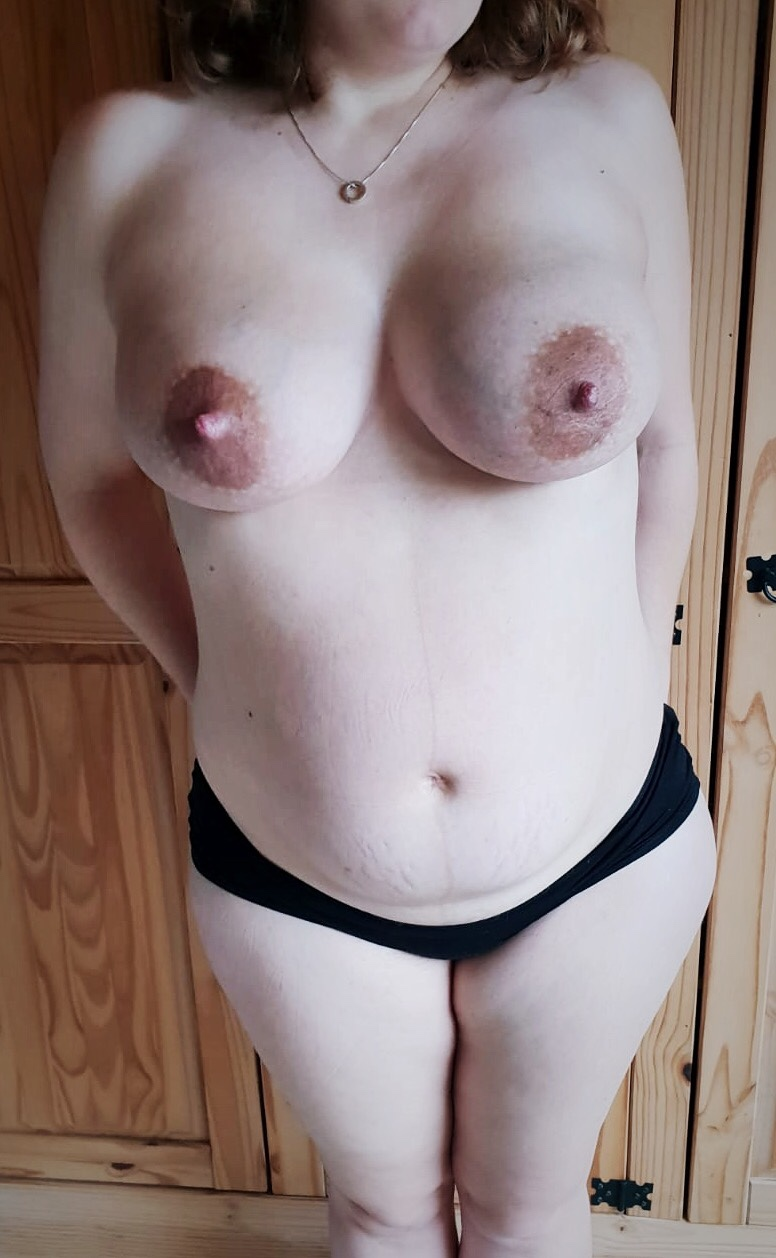 A frontal photo of my postpartum body, revealing my soft belly with linea nigra and stretch marks. My breasts appear swollen, especially the left.